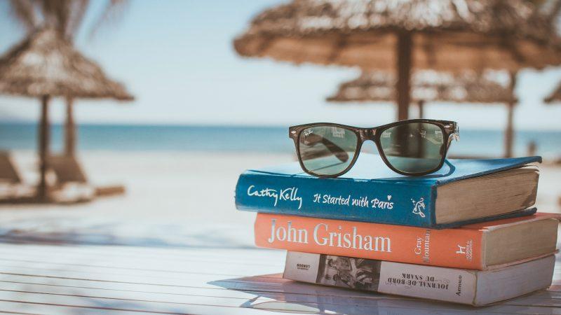 Pile de livres et lunettes soleil sur le bord de la plage