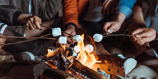 gens qui font griller des guimauves autour d'un feu de camp