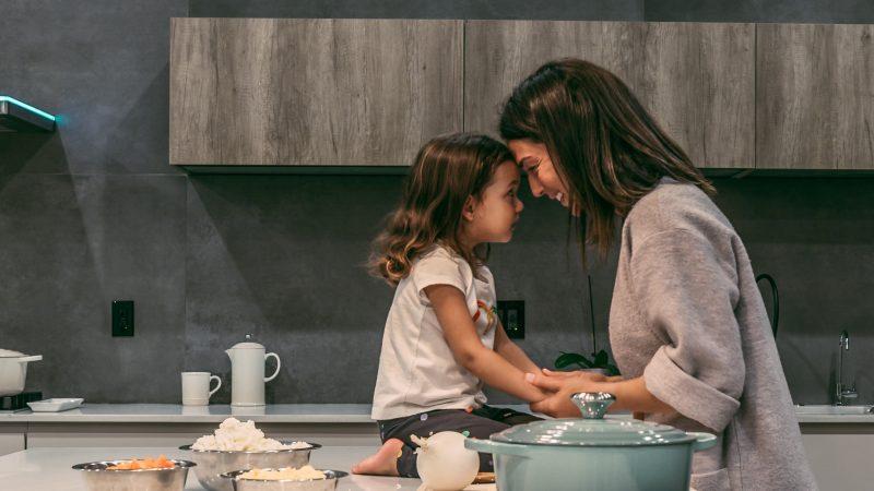 femme debout le front collé sur celui d'une petite fille assise sur un comptoir de cuisine